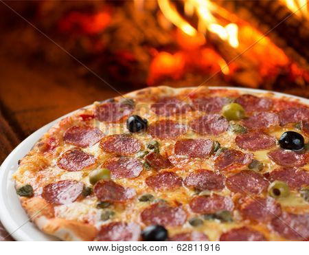 Traditional pizza with salami , capers and olives baking in oven