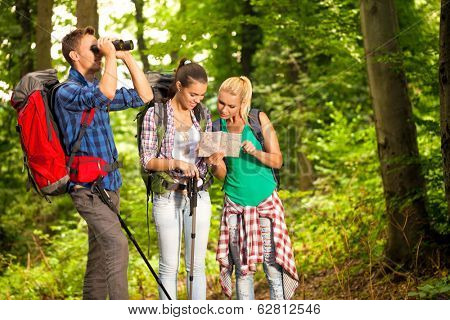 group of young hikers with map and binoculars on hiking, adventure orientation