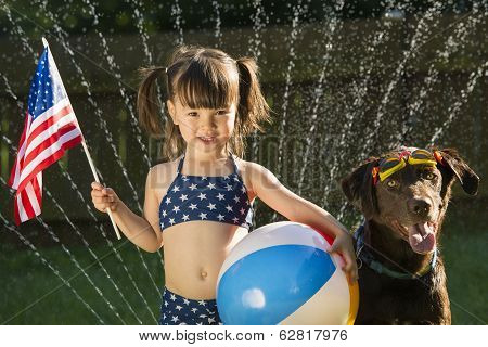 Preschooler Holding Us Flag And Beachball Posing With Dog