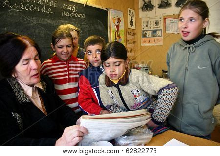 School Class In The Russian Village School Children Pupils Gathered Around A Schoolteacher.
