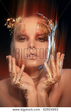 Art project: beautiful woman with golden make-up over black background. Jewelry, make-up. Fashion. Light effects.