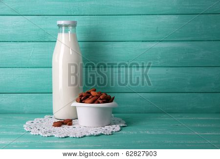 Almond milk in bottle with almonds in bowl, on color wooden background