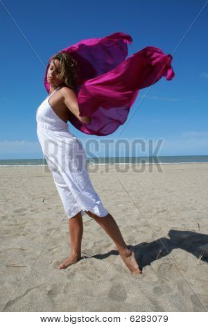 Young Women In White On Beach With Red Fluttering Scarf