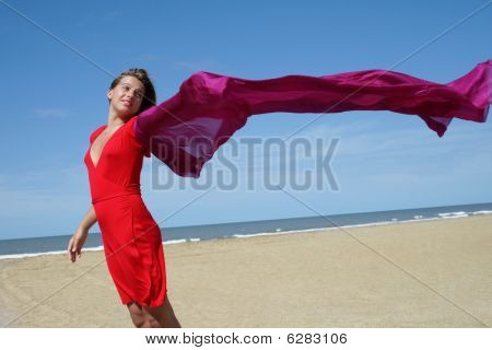 Young Women On Beach With Red Fluttering Scarf