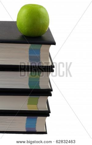 Stack of encyclopedias with green apple on top isolated on white