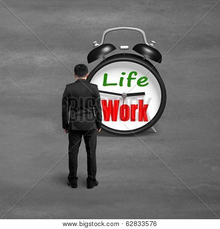 Standing Toward Alarm Clock With Life And Work Face