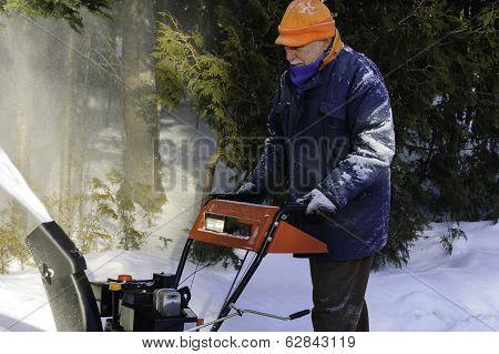 Senior Man Behind A Snowblower