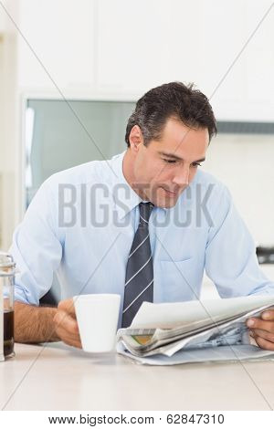 Serious well dressed man with coffee cup reading newspaper in the kitchen at home