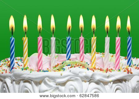 Birthday cake with colorful candles on a green background.
