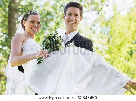 Happy groom carrying bride while looking away in garden