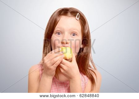 Excited Playful Young Girl Eating An Apple