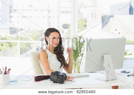 Beautiful focused photographer working at her desk in creative office