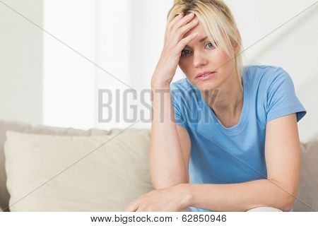 Worried young woman sitting in the living room at home