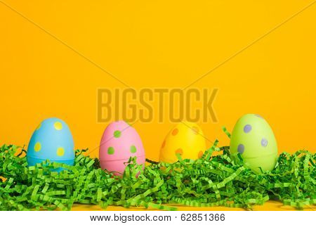 4 assorted colored Easter eggs on a yellow background