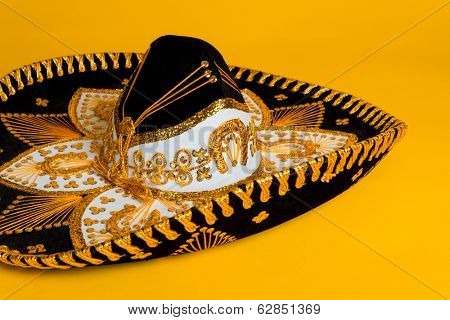 Ornate black, gold and white Mexican sombrero on a bright yellow background