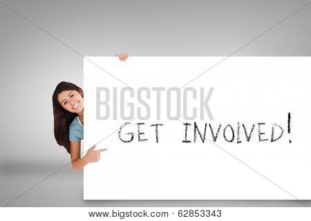 Pretty brunette showing card with get involved against grey background