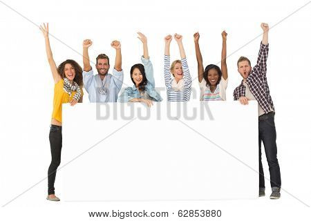 Smiling group of young friends showing large poster and cheering on white background