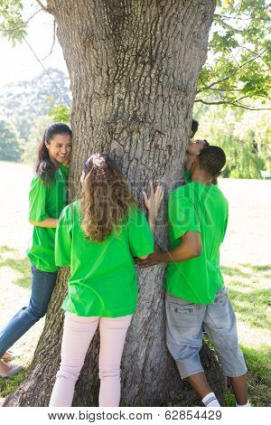 Group of environmentalists standing around tree trunk in park