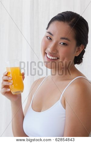 Pretty asian woman holding glass of orange juice at home in the living room