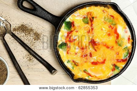 Skillet Baked Eggs with Brocoli, Cheese, Sriracha Sauce on Table.