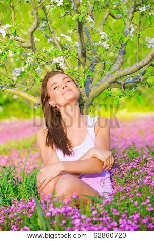 Beautiful calm girl with closed eyes sitting down on pink floral glade under blooming apple tree, relaxation outdoors in spring time