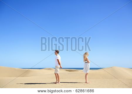 Relationship problem - upset couple argument. Angry couple in disagreement divorce and separation concept. Young couple with marriage problems. Woman and man conceptual image in desert under blue sky.