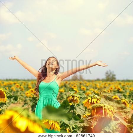 Woman summer girl happy in sunflower flower field. Cheerful multiracial Asian Caucasian young woman joyful, smiling with arms raised up.