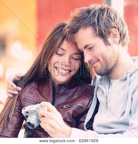Couple looking at pictures on camera. Beautiful young lovers having fun together outside looking at photos on vintage retro camera. Interracial couple, Asian woman, Caucasian man.