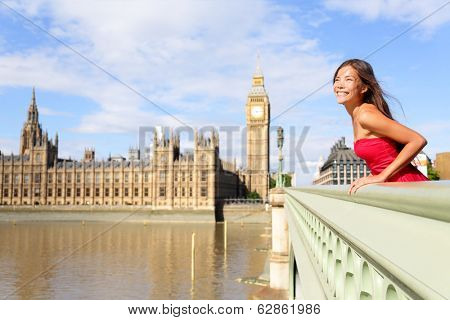 London woman on Westminster Bridge by Big Ben, England. Beautiful tourist girl sightseeing travel on Westminster Bridge, London, England, United Kingdom. Elegant multiracial female model in red dress.