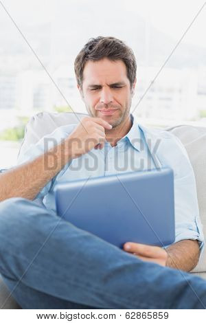 Thinking man sitting on the couch using his tablet at home in the living room