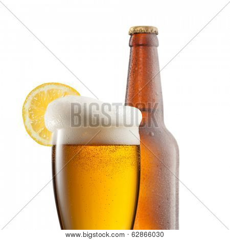Beer in glass with lemon and bottle isolated on white