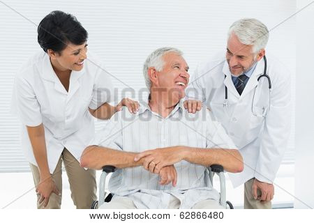 Happy senior patient with doctors sitting in wheelchair at the hospital
