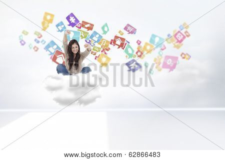Woman looks straight ahead as she celebrates in front of her laptop against clouds in a room