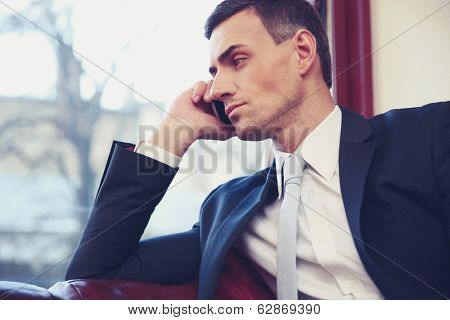 Confident businessman talking on the phone and looking in window at office