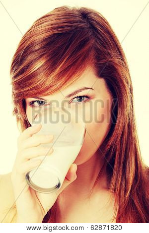 Young beautiful teen woman drinking milk
