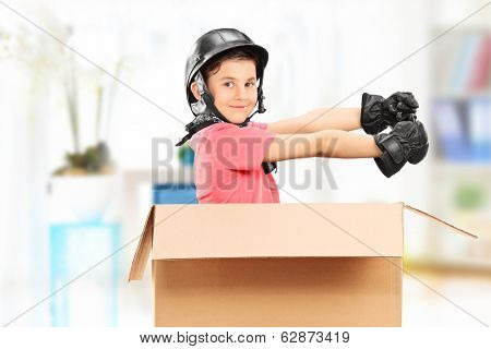 Playful boy sitting in a box at home