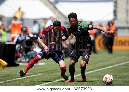 CARSON, CA - APRIL 6: Chivas USA D Eric Avila (15) & Los Angeles Galaxy M Baggio Husidic (6) during the MLS game between the Los Angeles Galaxy & Chivas USA on April 6th 2014 at the StubHub Center.