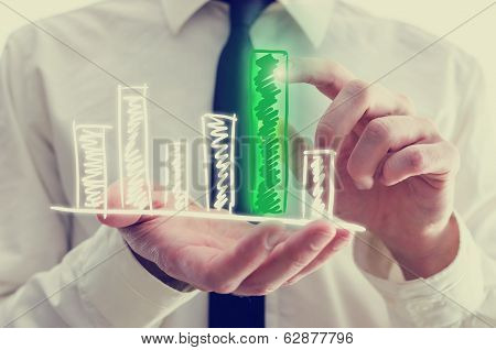 Businessman Holding A Bar Graph In His Hand