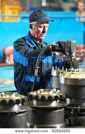 adult industrial worker during heavy industry machinery assembling on production line manufacturing workshop at factory