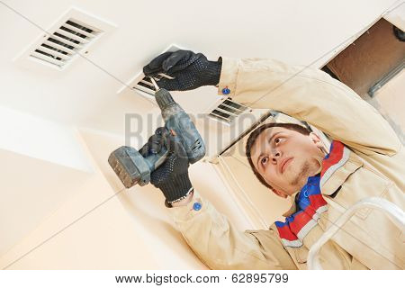 industrial builder installing ventilation or air conditioning filter holder in ceiling