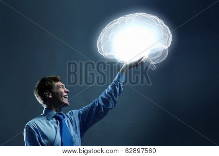 Young man holding human brain in hand