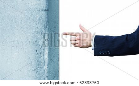 Businessman in suit pointing at huge stone