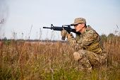 stock photo of rifle  - Soldier with a rifle in the field - JPG