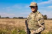 foto of armor suit  - Soldier with a rifle in the field - JPG