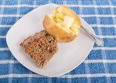 image of meatloaf  - Fresh home made meatloaf on a white plate with a buttered baked potato - JPG