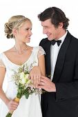 Happy bride and groom wearing wedding rings while looking at each other over white background