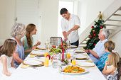 pic of christmas meal  - Father serving Christmas meal to family at dining table - JPG