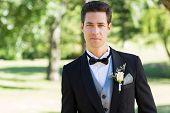 Portrait of confident groom in tuxedo standing at garden
