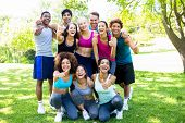stock photo of sportswear  - Group of friends in sportswear showing thumbs up at the park - JPG
