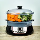Healthy food in steamer, steam cooker with pumpkin and broccoli